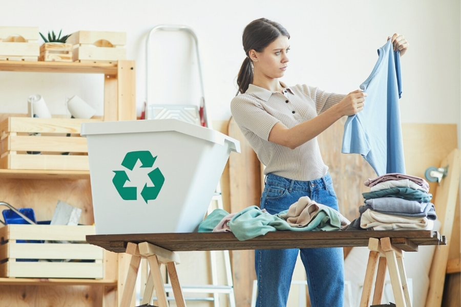 Woman selecting clothing to recycle
